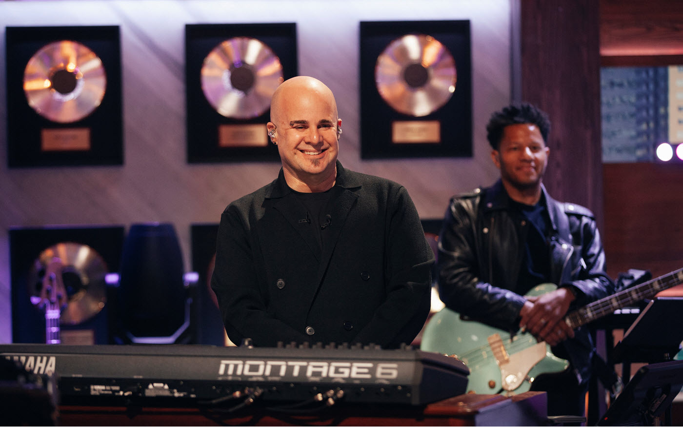 Attractive young bald male musician with a guitarist in the background and a wall of framed gold albums smiles for camera.