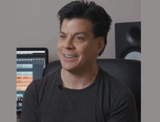 Man smiling for camera with home studio in background.