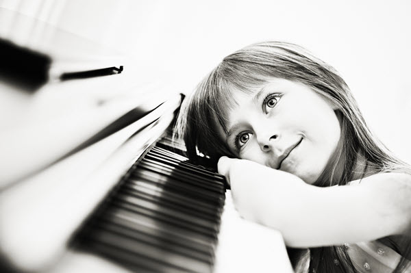 Black and white image of a young girl smiling while resting her arm and head on her piano keys.