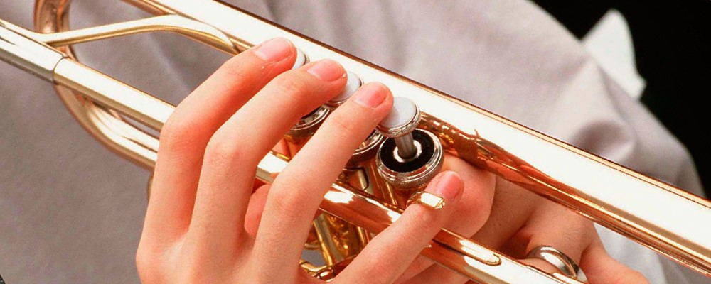 Closeup of someone's hands as they play trumpet.