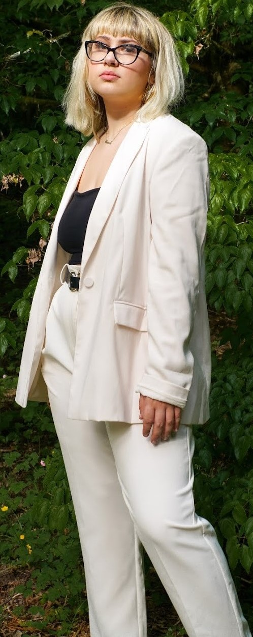 Young woman in a white pant suit with black blouse and glasses.