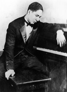 Man in tuxedo sitting at a piano.