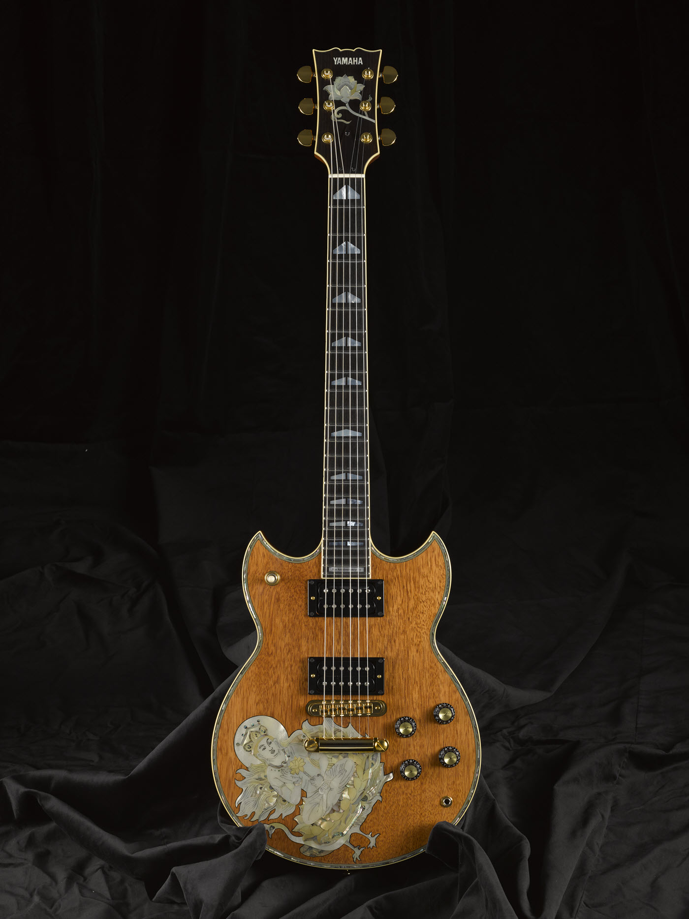 Electric guitar with embellishment on face.