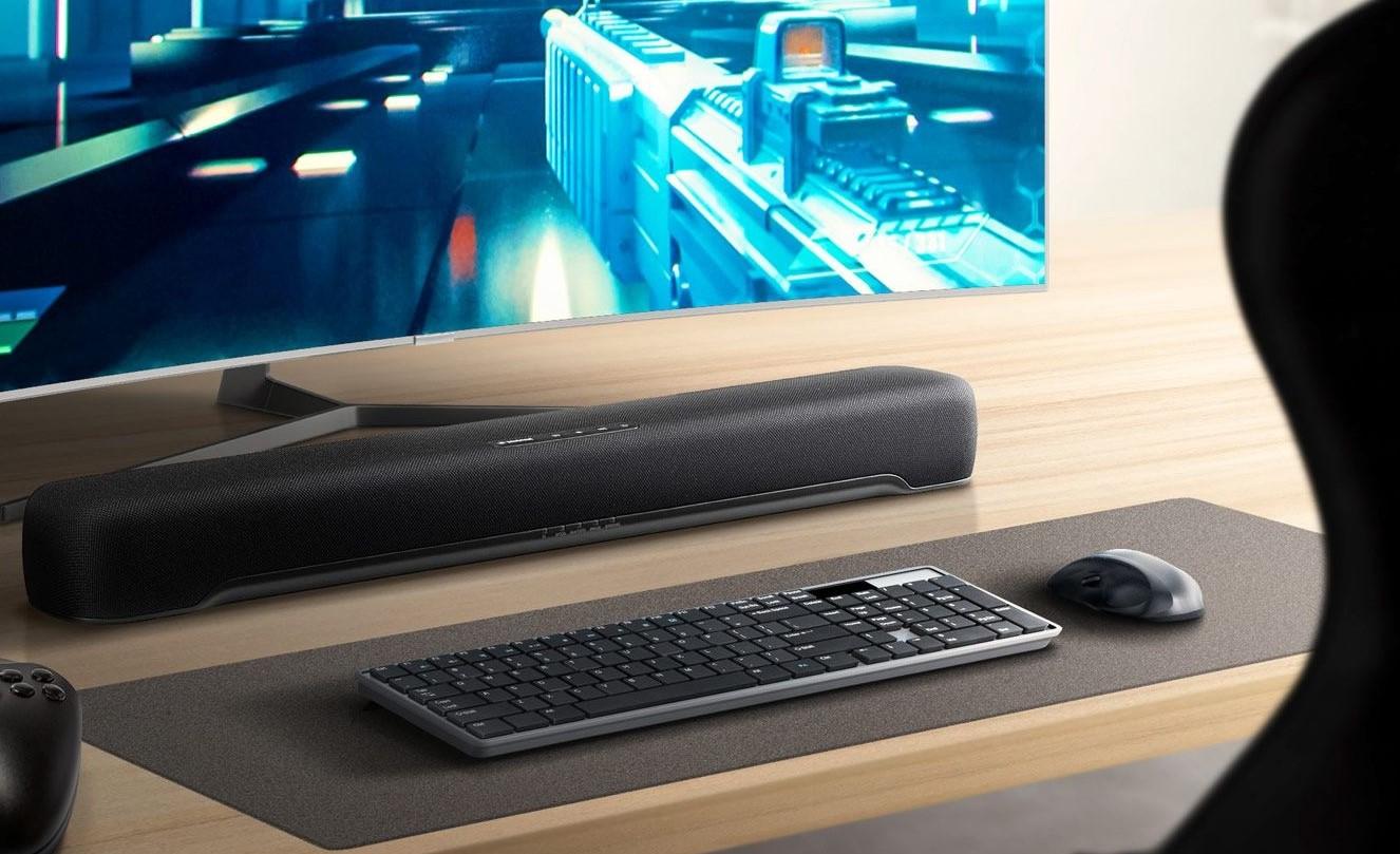 Closeup of a sound bar under a computer screen on a desk.