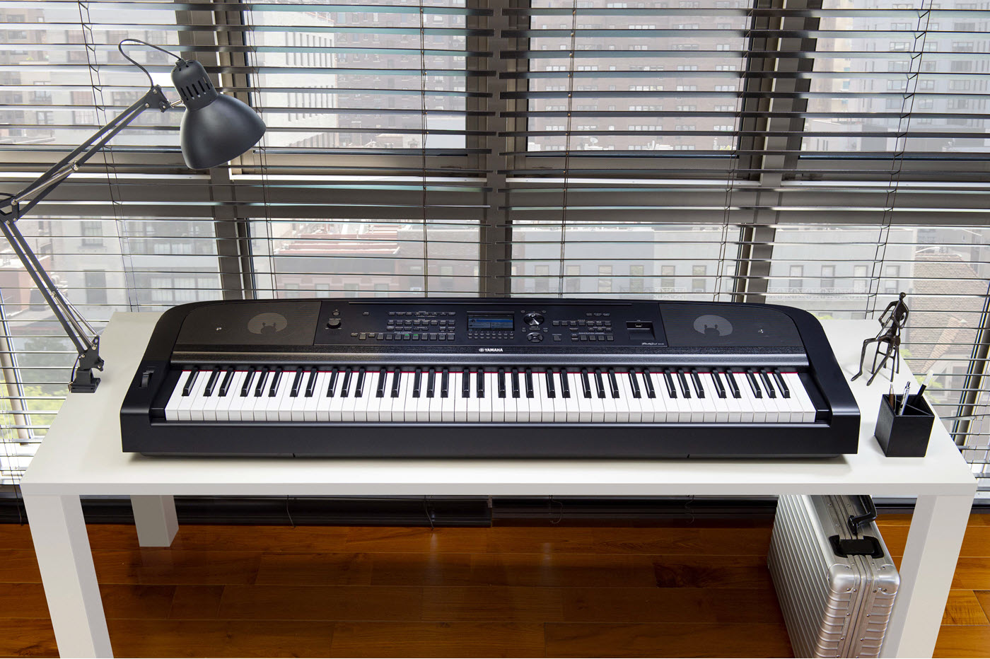 Digital piano keyboard on a desk in front of a window in a highrise apartment.