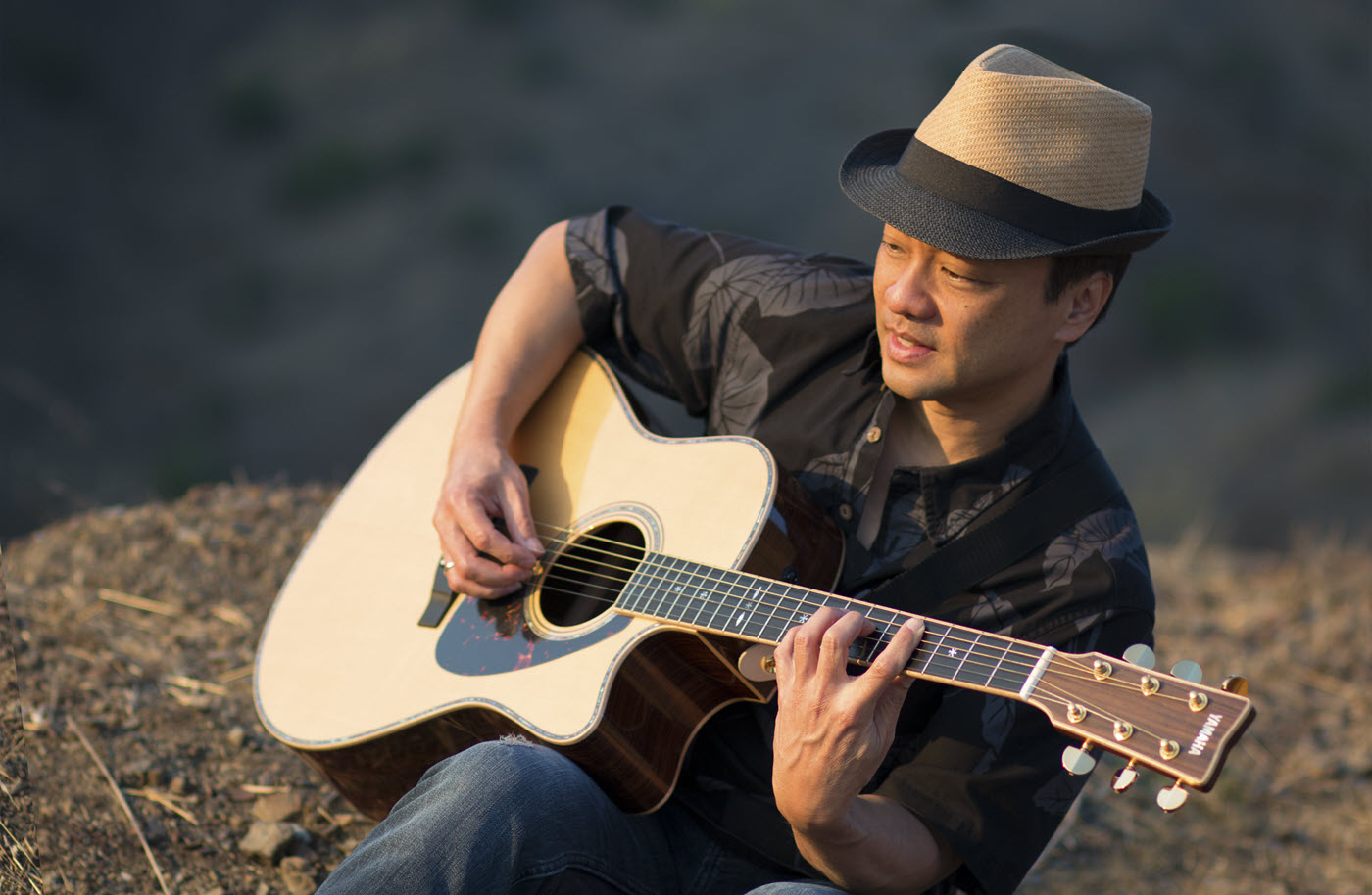 Young man in hat playing an acoustic guitar.