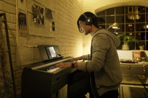 Boy playing a digital piano while wearing headphones.