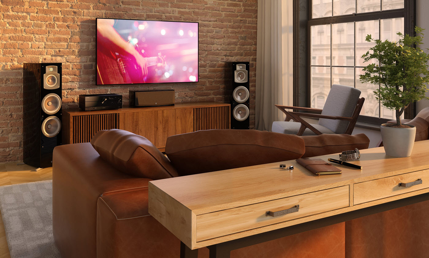 Modern living room with couch facing large flat screen TV. The TV is flanked by tall speakers.