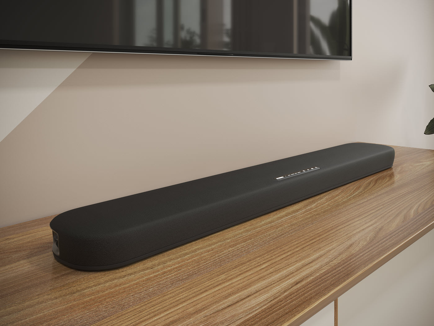 Long thin speaker laying on a counter underneath a flat screen TV which hangs on the wall above it.