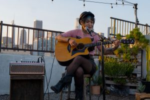 Young woman playing guitar on rooftop.