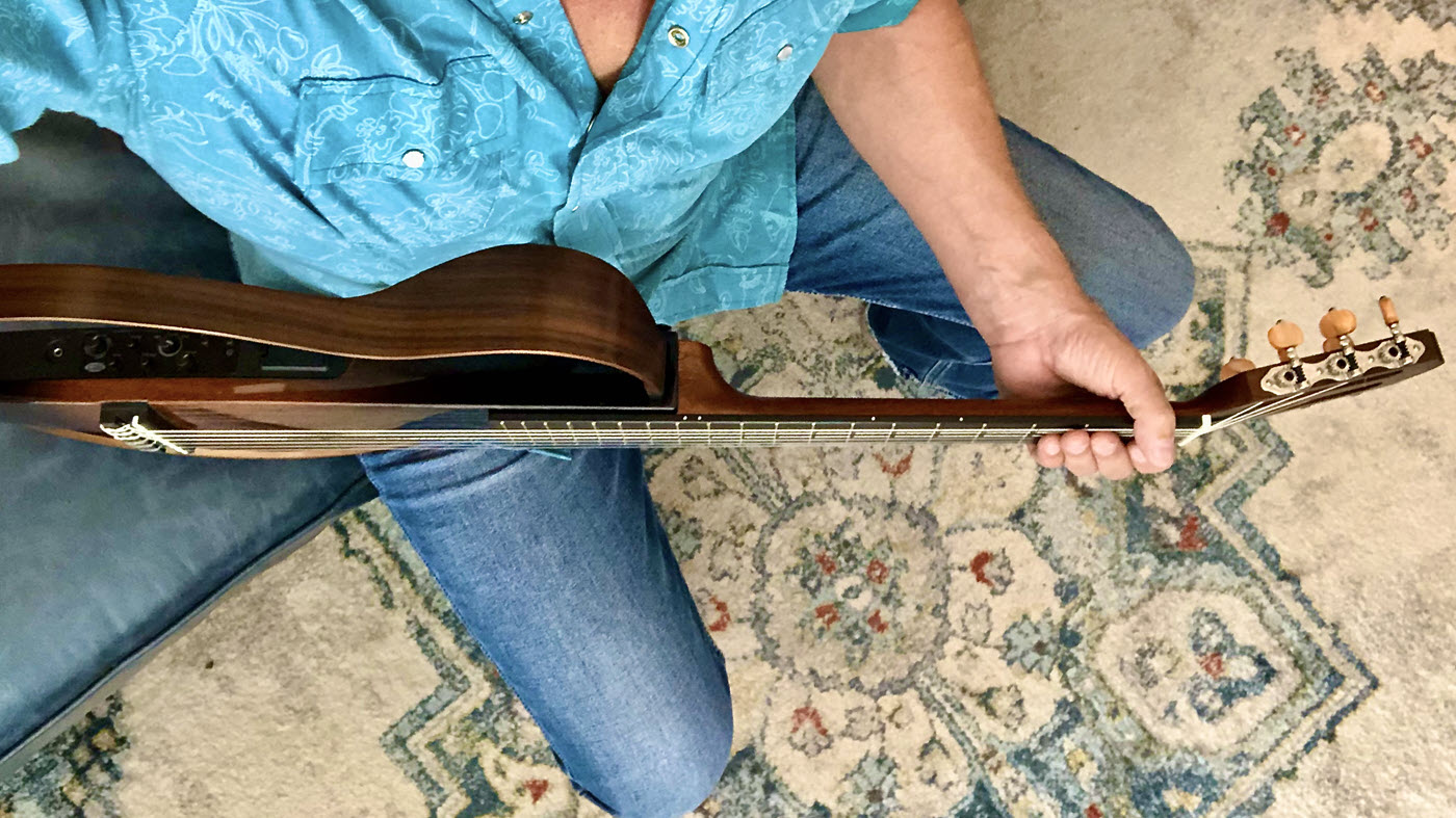 Seen from above a closeup of the position of the hand and wrist high on the neck of the guitar.
