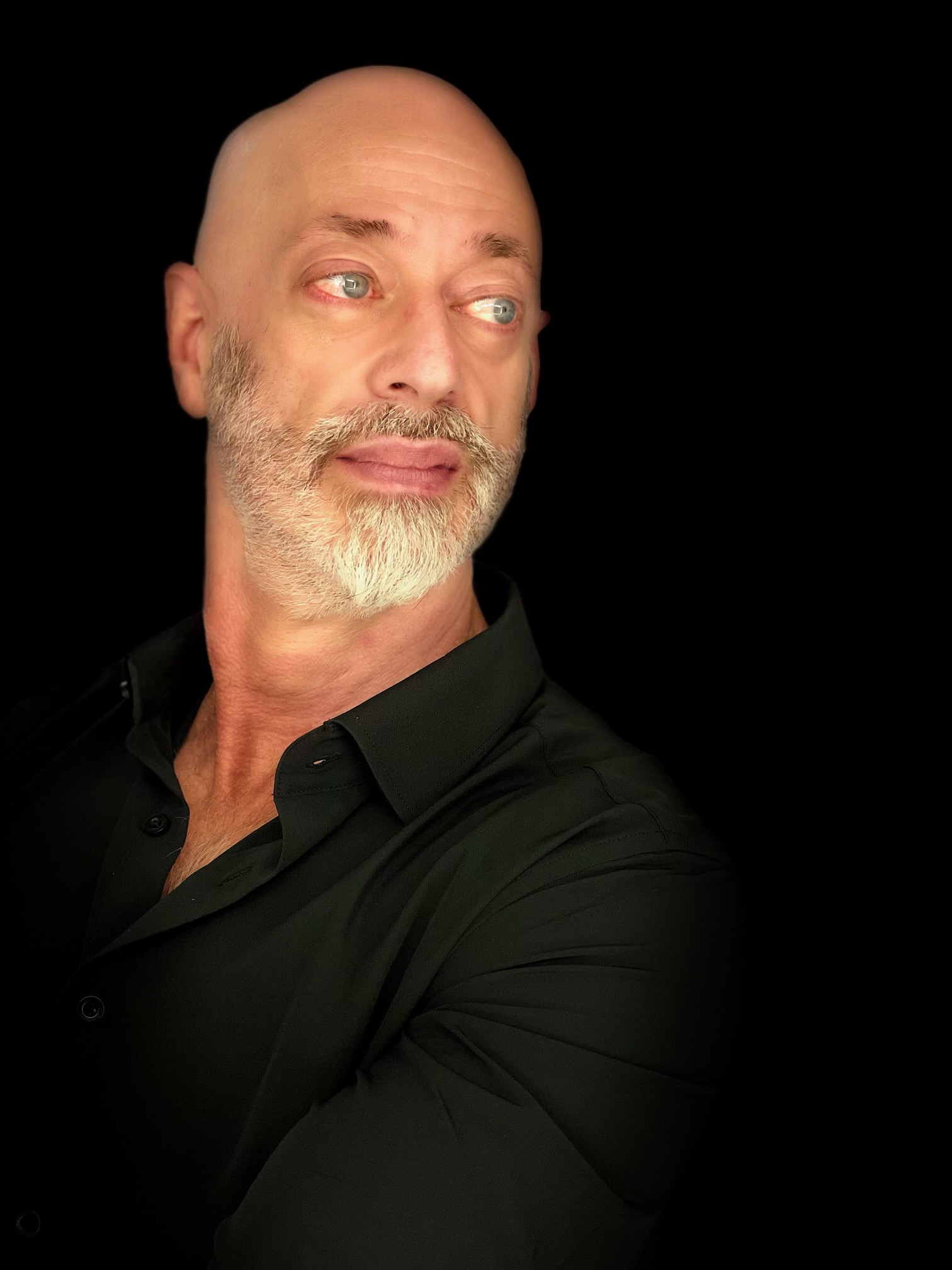 Bald-headed man with cropped white beard in a black button up shirt looking over his left shoulder.