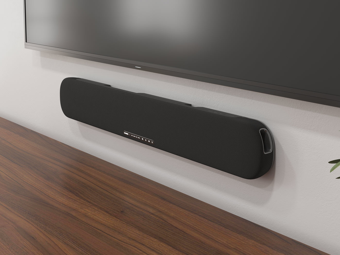 Close-up of a long thing speaker mounted on the wall horizontally under a flat screen TV.