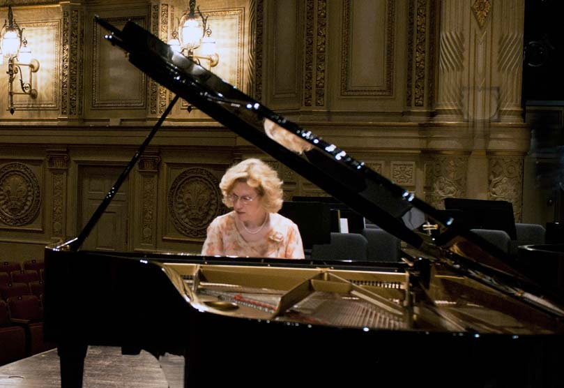 Middle-aged woman with light hair and glasses playing a grand piano on stage.