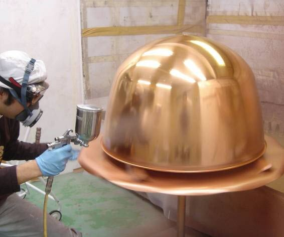Person wearing PPE spraying lacquer on an inverted timpani bowl.