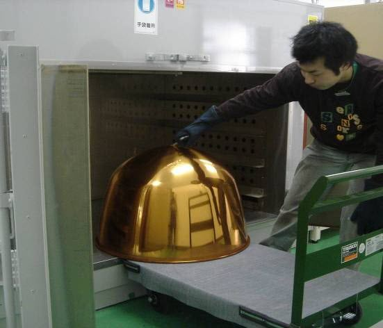 Man moving a timpani bowl into or out of a large metal cabinet.