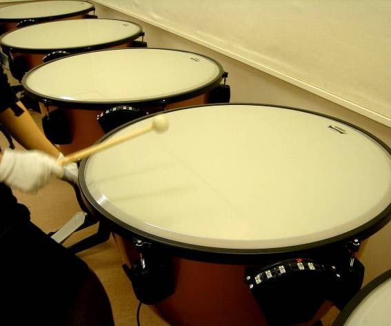 Closeup of a line of timpani being played.