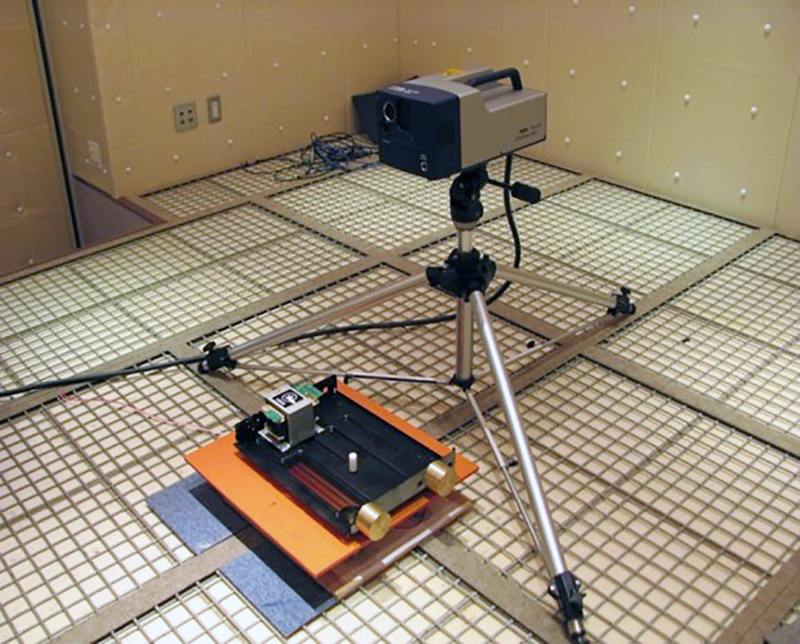 Tripod holding a small rectangular unit in a room with a grid-tracked floor. There is a small electronic unit on a pad that is on grid track in front of the unit on a tripod.