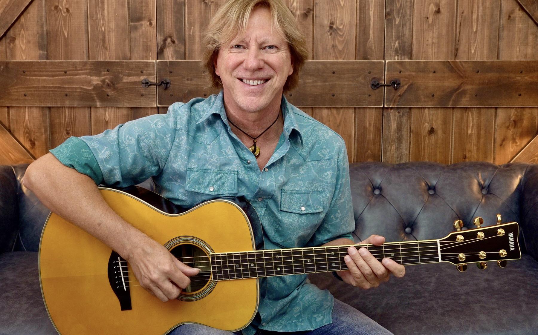 Man smiling and playing guitar.