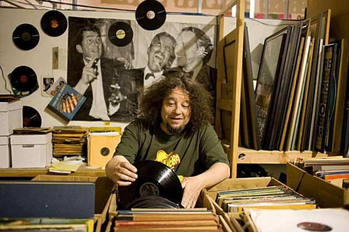 Man in graphic t-shirt and curly hair looking through collection of vinyl.