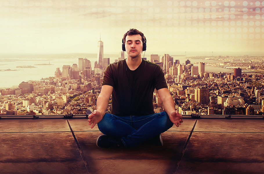 Man sitting in a lotus position meditating on on a roof with a cityscape behind him. He is wearing headphones.