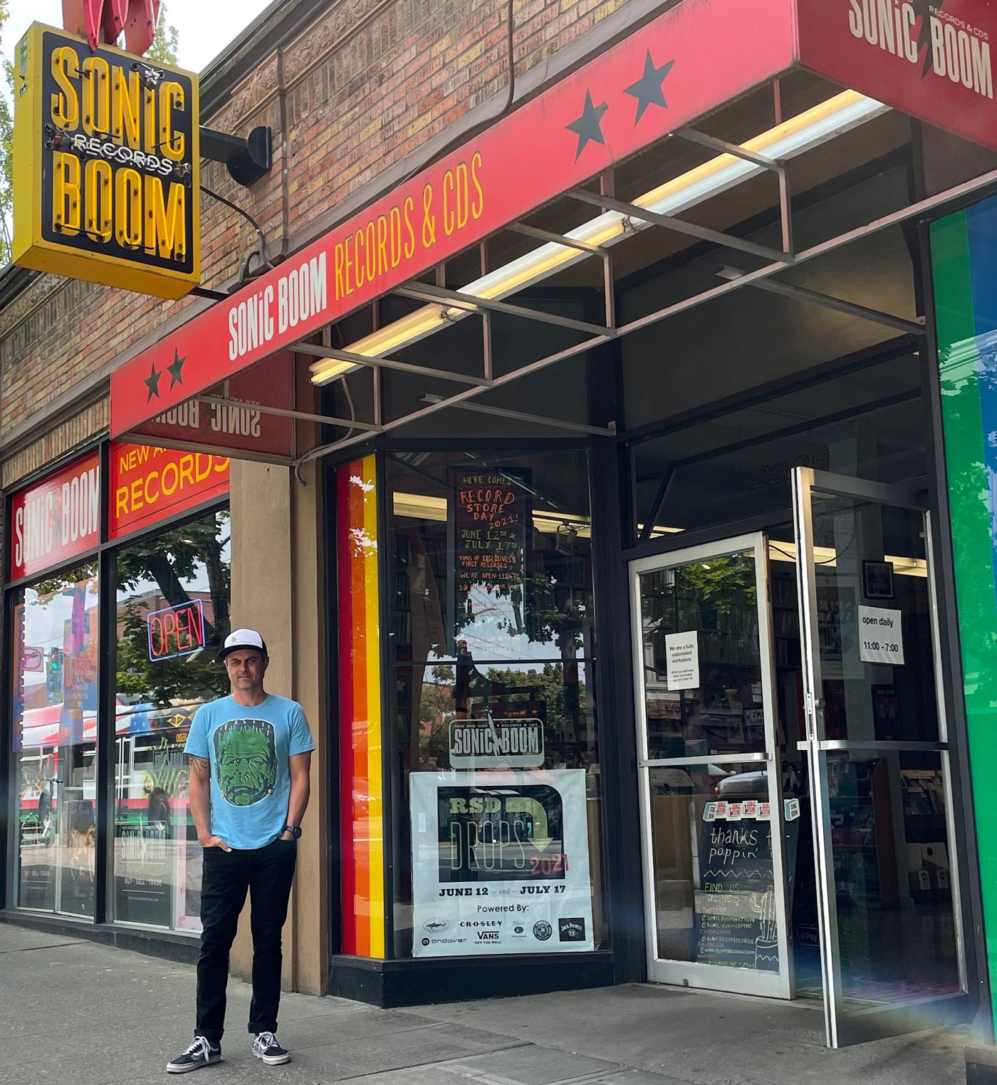 """Man in graphic t-shirt, jeans and cap standing in front of urban record store with signage indicating it is """"Sonic Boom Records & CDs""""."""