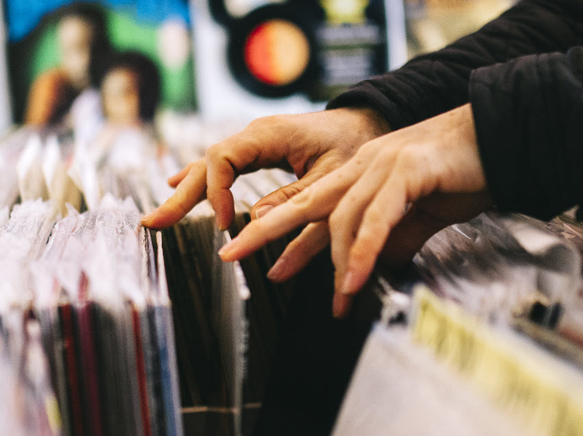 Closeup of someone's hands as they dig through record stacks in a store.
