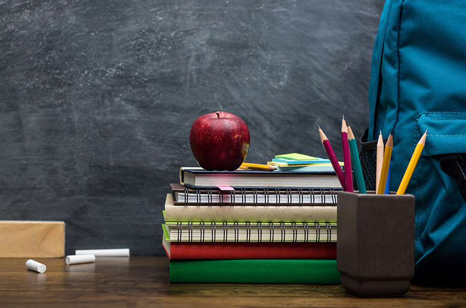 Stack of notebooks with an apple on top next to a pencil holder and books. with a piece of broken chalk all in front of a blackboard