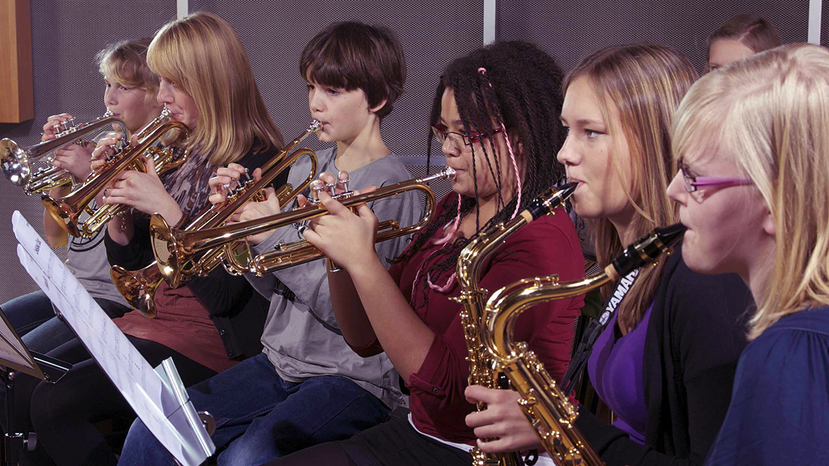 Young people rehearsing as a school band.