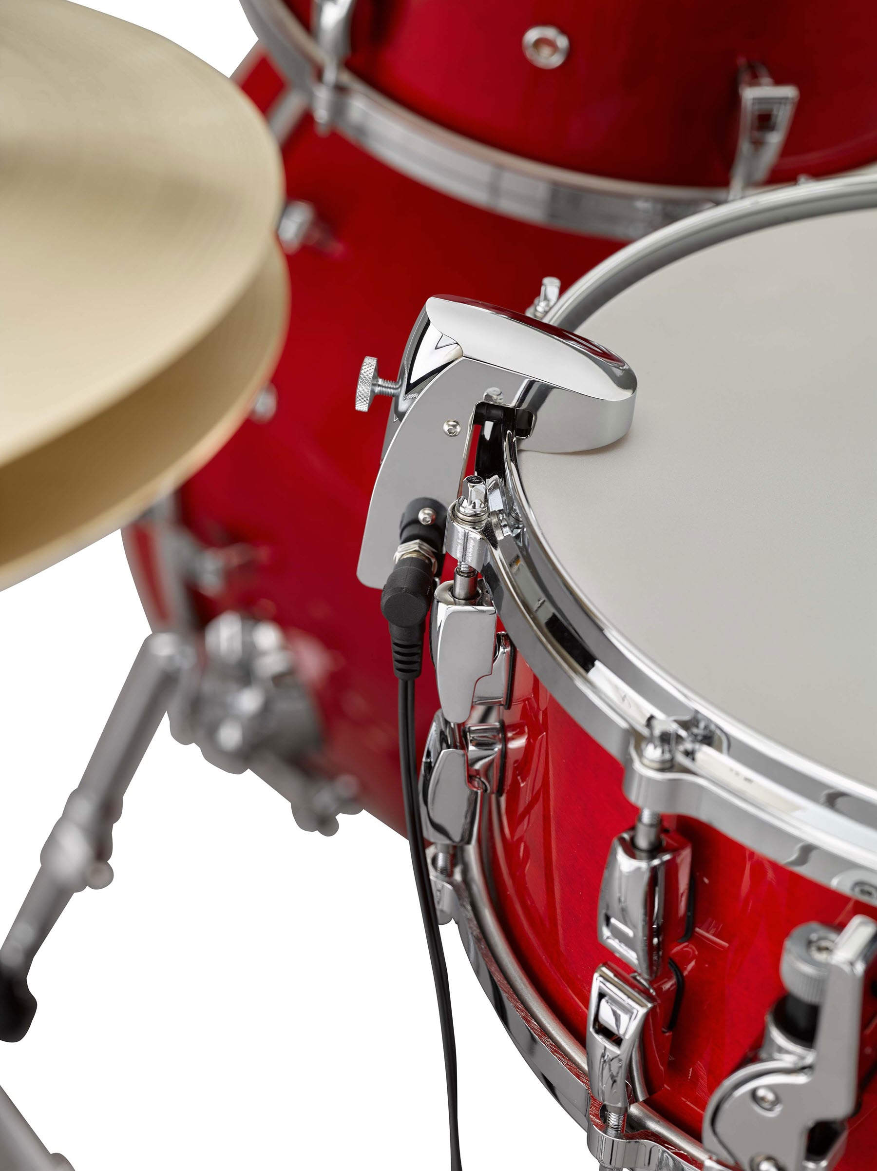 Closeup of a snare drum with sensor attached.
