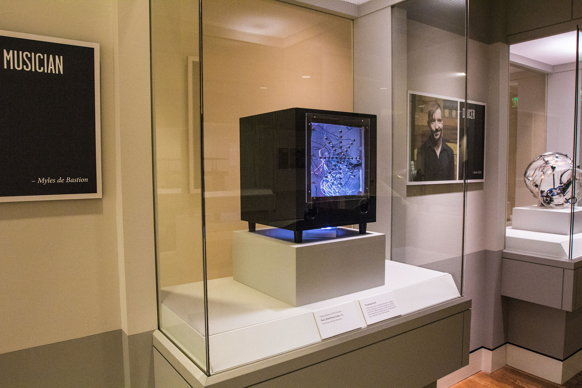 Electronic box with a screen inside a glass museum case.