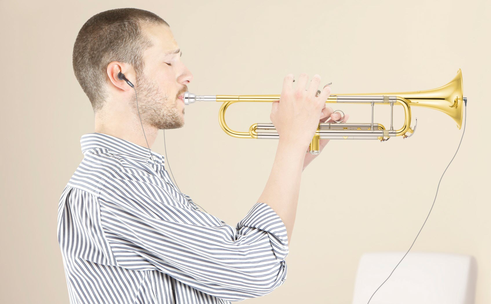 Young man playing a trumpet in a living room while wearing earbuds.