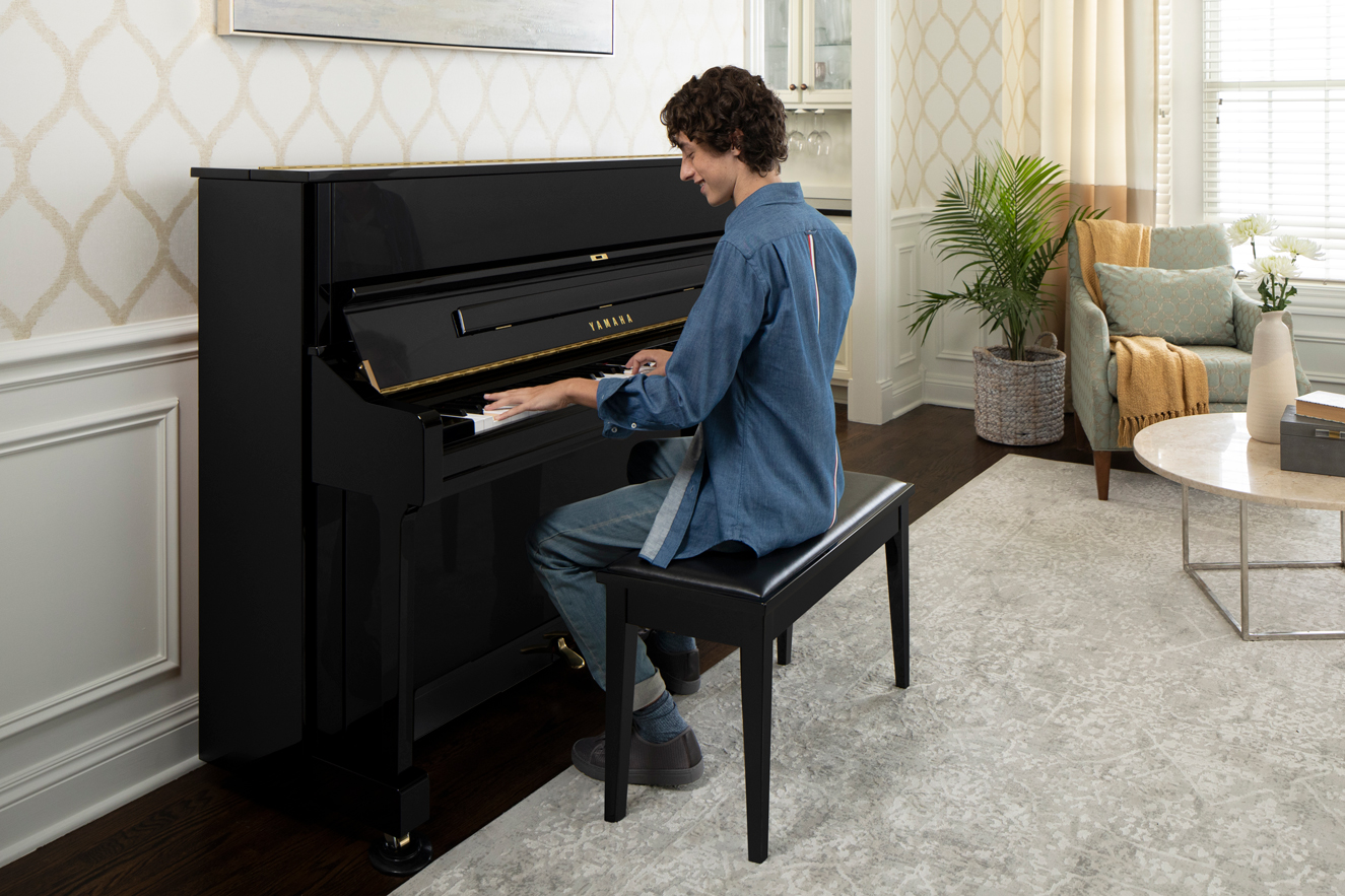 Woman playing an upright piano in a home.