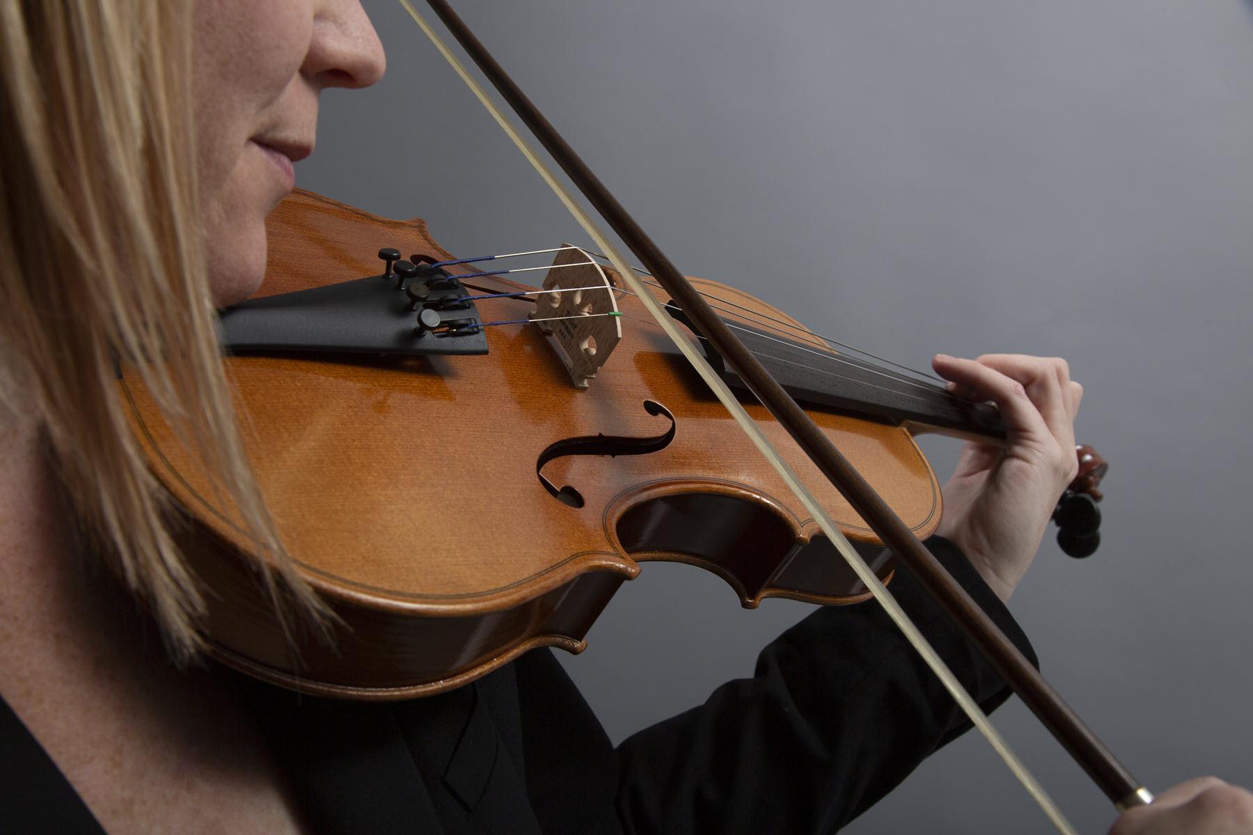 Closeup of young woman playing violin.
