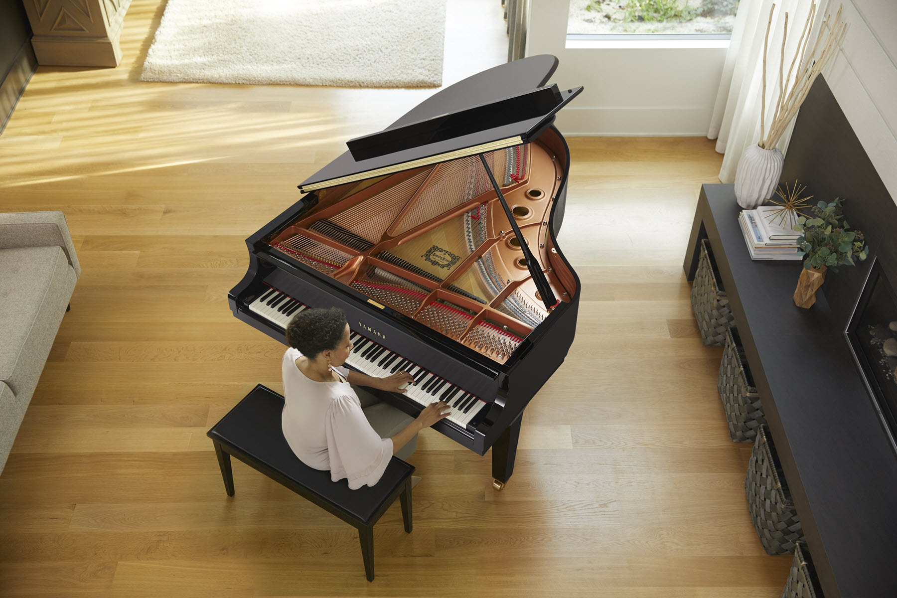 Someone playing a grand piano in a living room as seen from above.