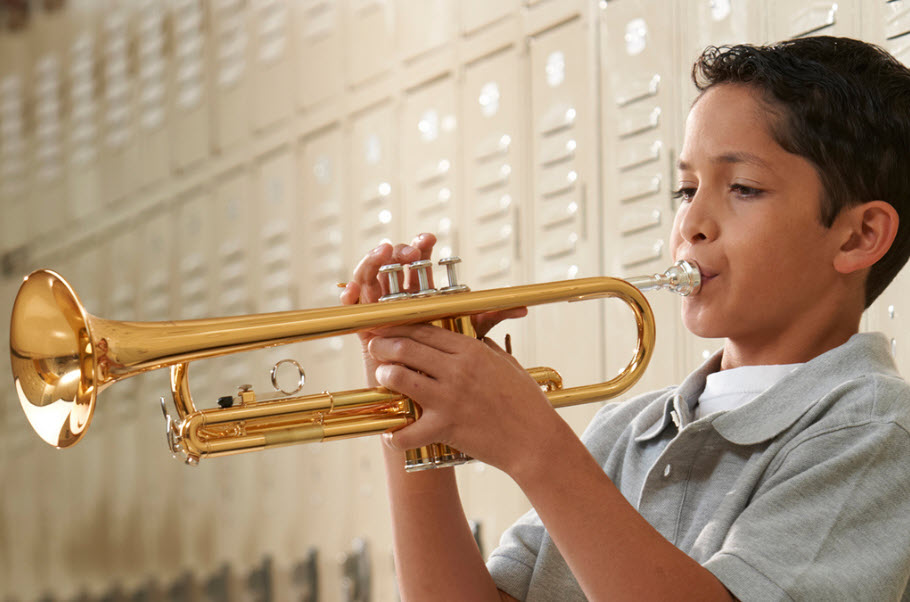 Young boy playing a trumpet in front of school lockers.