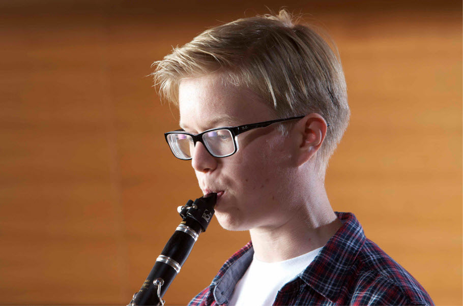 Young boy playing a clarinet.