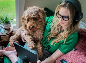 A girl wearing headphones with a dog on her lap watching a movie on a tablet.