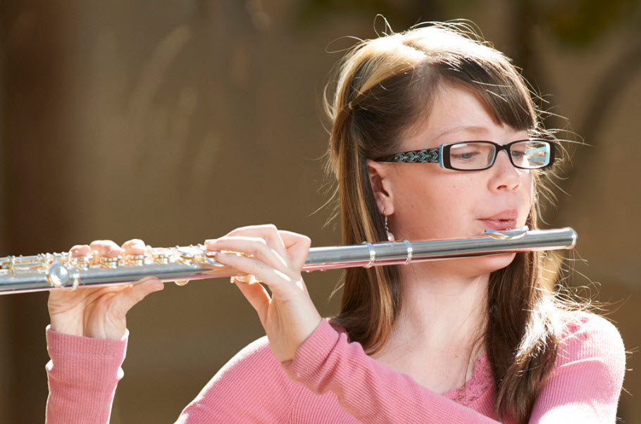 Young girl playing a flute.