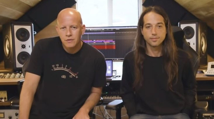 Two men, one bald and one with long hair, sit in front of a digital audio studio setup.