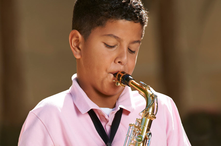 Young boy playing a saxophone.