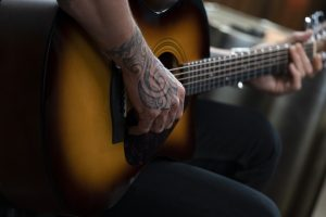 Closeup of Keith Urban's tattooed arm and hand holding the guitar by the neck.