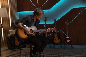 View of Keith Urban playing an acoustic guitar.