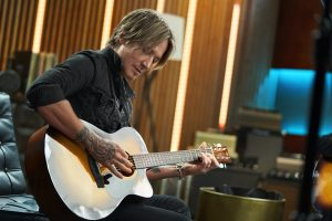 Keith Urban playing an acoustic guitar.