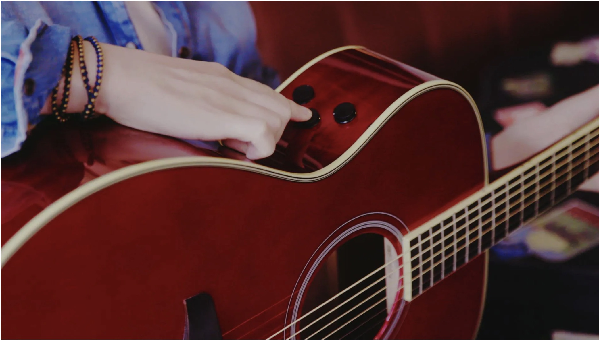 A closeup of someone pointing out the knobs on side of hybrid acoustic guitar.