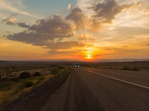 Empty highway leading into a sunset.