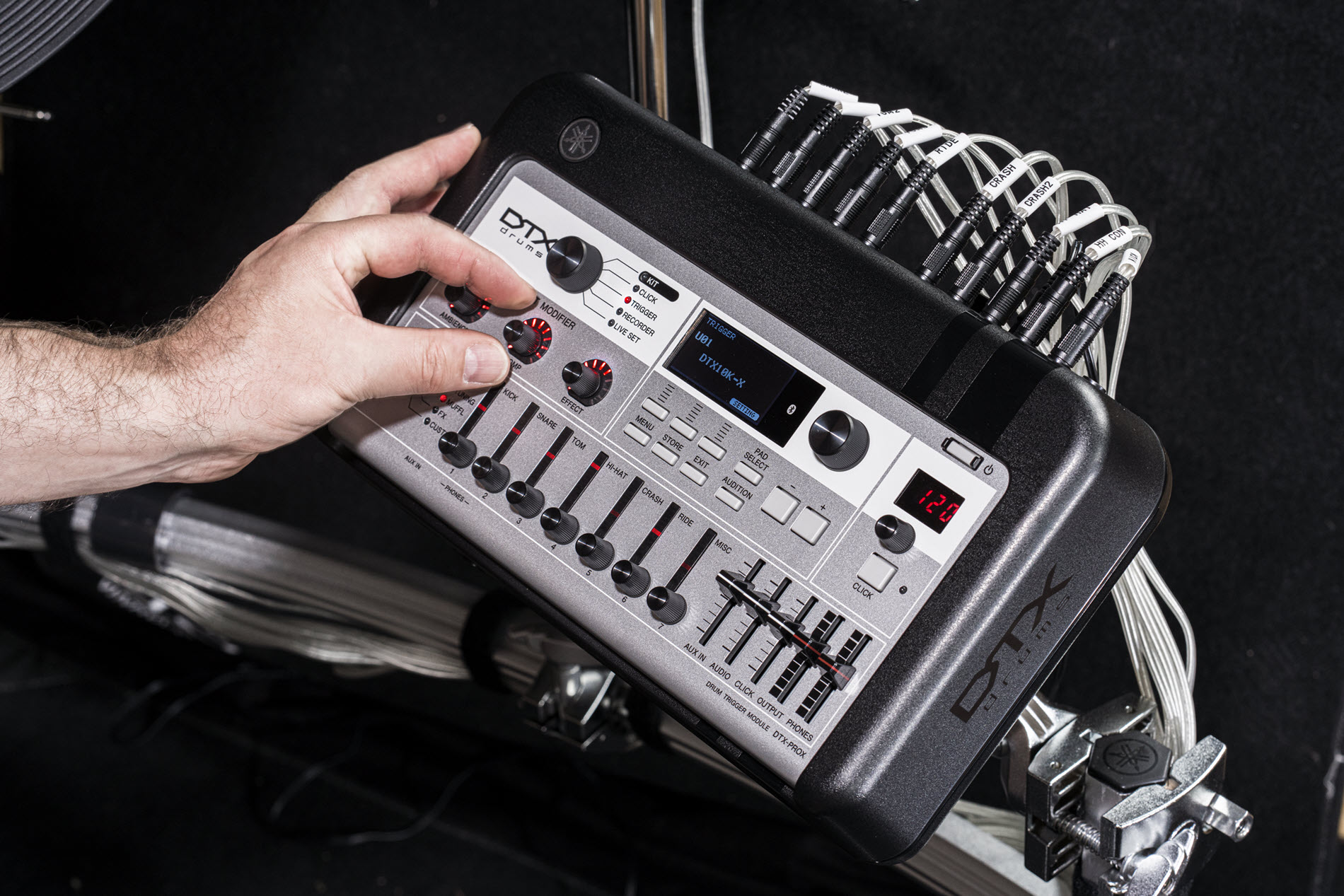Closeup of someone's hand adjusting the dials on the electronic drum kit.