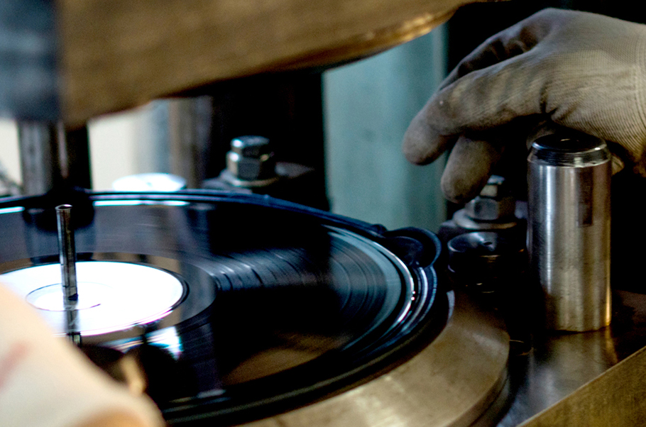 Closeup of a vinyl record being pressed.
