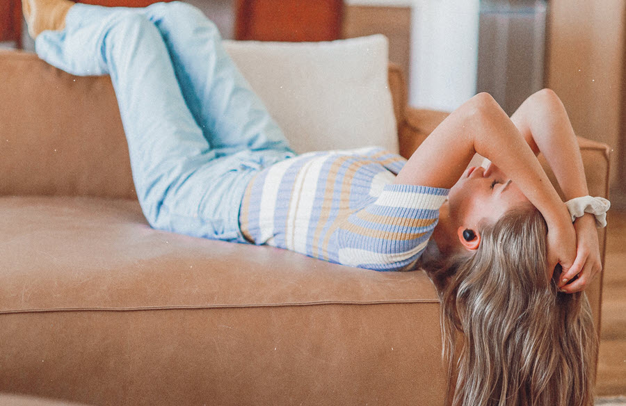 Young woman sprawled on couch wearing earbuds.