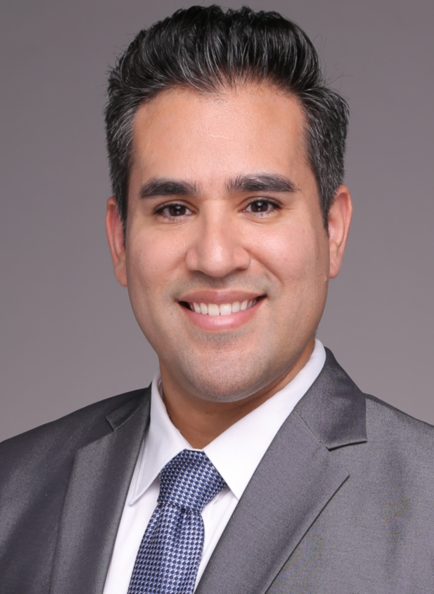 Professional headshot with man in suit and tie smiling for camera.